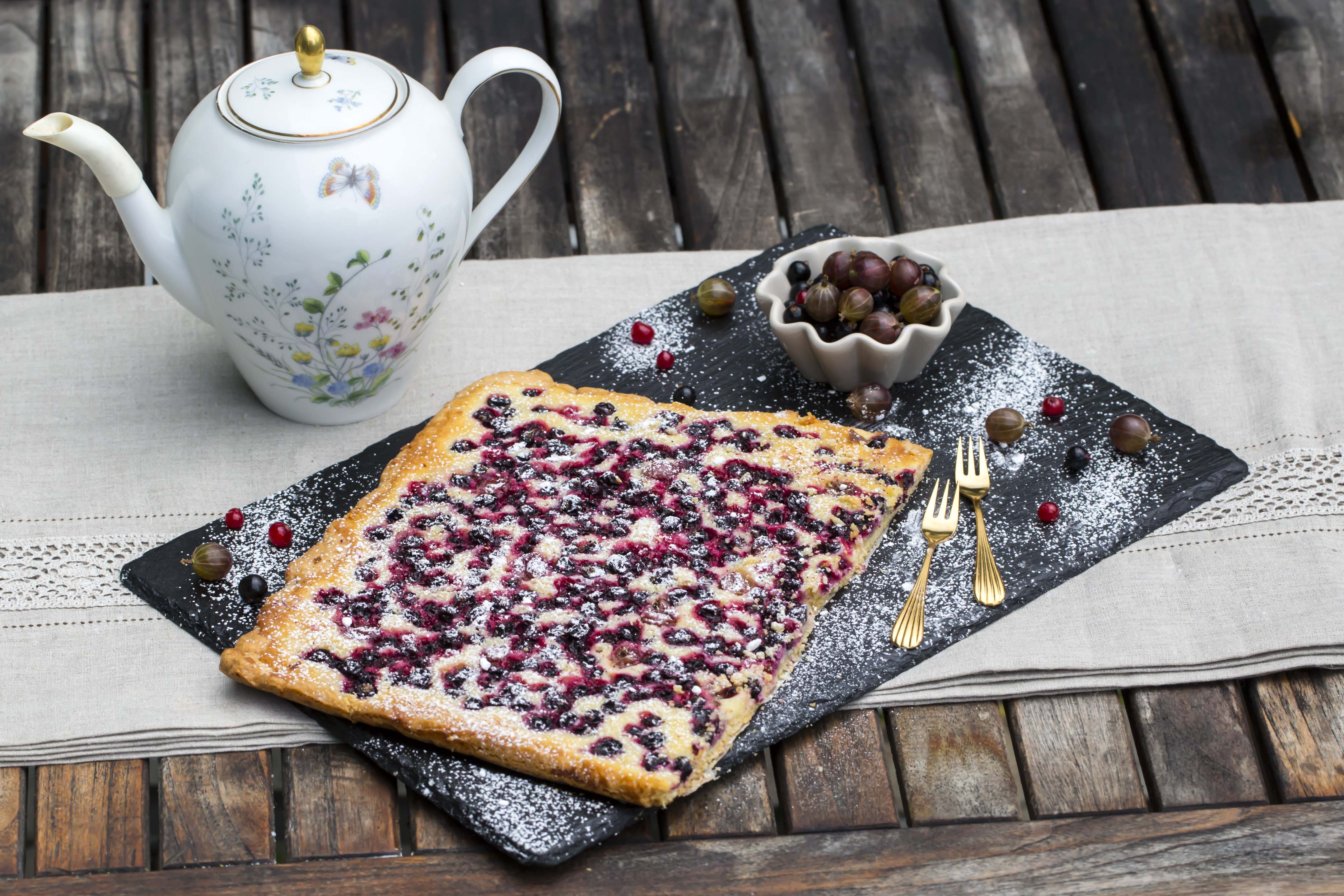 Blechkuchen mit Beeren auf einer dunklen, mit Puderzucker bestäubten Schieferplatte. Daneben ein Schälchen mit Johannis- und Stachelbeeren. Im Hintergrund eine Kaffeekanne.